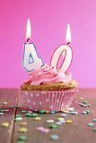 40 birthday cupcake. Number forty birthday candles on a pink cupcake on a wooden table Stock Photo