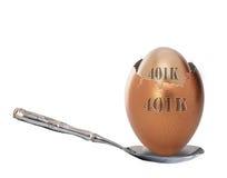 401k retirement nest egg. Cracked 401k retirement nest egg in silver spoon, isolated on white background Royalty Free Stock Images