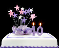 40th Cake. Fancy cake with number 40 candles.  Decorated with ribbons and star-shapes, in pastel tones on black background Stock Photo