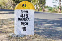 413 kilometers to Dwarka milestone. Rural landscape in Gujarat India incorporating 413 kilometers to Dwarka milestone and land mark on the coastal road from Royalty Free Stock Photo