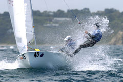 420 Sailing. 420 sailors crash through a small wave as they head out to sea Stock Photo