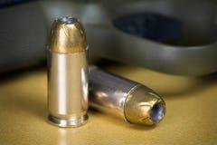 .45 Caliber Hollow Pistol Bullets Near Handgun. 45 Caliber Hollow Point Pistol Bullets Standing Near Handgun on gold colored background Stock Image