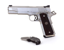 45 caliber pistol and knife. A 45 caliber semi-auto pistol and automatic knife Royalty Free Stock Photos