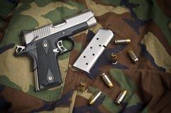 45 Feuerwaffe, Pistole-Klipp, Gewehr-Munition auf Camo Stockbilder