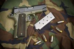 45 Feuerwaffe-Pistole-Klipp und Handgewehr auf Tarnung Stockfoto