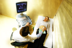4D Pregnancy Ultrasonic Scan. Obstetrician examining pregnant belly by 4D ultrasonic scan stock photo