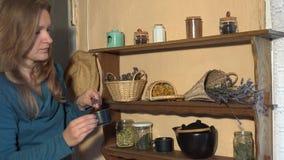 Η γυναίκα υπόβαλε το θυμάρι μεντών φλυτζανιών βοτανικό από τα ράφια στην κουζίνα 4K απόθεμα βίντεο