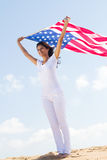 4th July. Concept: Young happy beautiful woman holding a USA flag outdoors stock image
