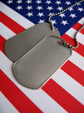 4th July Dog Tags. Dog tags and the flag of America. Focused on the dog tags Royalty Free Stock Image
