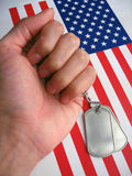 4th July Dog Tags. Dog tags and the flag of America. Focused on the dog tags stock image