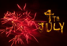 4th July fireworks. Pink explosion of fireworks and sparkler writing of 4th July Royalty Free Stock Images