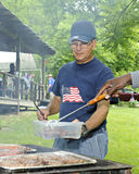 At a 4th of July Picnic Grill. A senior man grilling at a Fourth of July picnic Royalty Free Stock Image