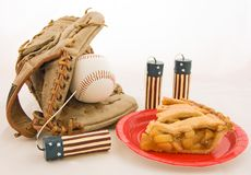 4Th Of July Still Life. American favorites for the 4th of July baseball apple pie mitt and red white & blue flag patterned candles on a light colored background Stock Images