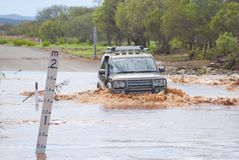 4WD crossing flooded road. 4x4 is slowly crossing flooded road next to a mark indecating waterlevel. Captured during rain season in Western Australia Royalty Free Stock Image
