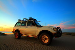 4WD on sand dune. White toyota 4WD on top of sand dunes with sunset back ground Royalty Free Stock Images