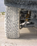 4wd tyre on sand. Close up of 4wd tyre on beach sand showing tyre tread and suspension Stock Photo
