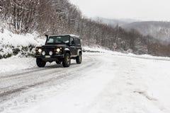 4x4 på den snöig vägen Arkivbild