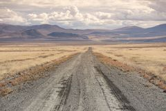 Dirt track stretches towards the horizon, Nevada,. Open road:  4x4 or off-road track stretching ahead into the distance through desert scrubland toward Stock Photography