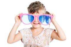 5-6 muchacha divertida de los años que desgasta los vidrios coloridos Imagen de archivo