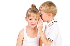 5-7 ragazzo di anni che bisbiglia alla ragazza Fotografie Stock Libere da Diritti