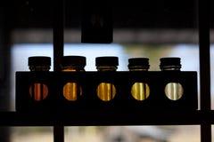 5 bottiglie con liquido in finestra Immagini Stock Libere da Diritti