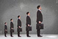 5 hållande portföljar för affärsmanar som står i en ro Arkivfoton