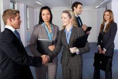 5 junge Geschäftsleute, Händedruckgeste Stockfoto