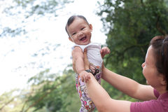 5 month old Chinese baby girl. Playing with mommy in the park Stock Image