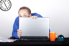 Almost 5 o'clock. Shy worker hiding behing his lap top at work royalty free stock photos