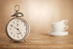 5 o'clock tea time, retro alarm white tea cups Royalty Free Stock Photos