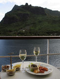 5 O'Clock Treats. Table of wine and appetisers on a cruise ship overlooking a view of a lush island Royalty Free Stock Photo