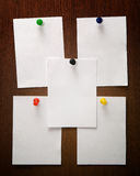 5 papers. Colored thumbtack, five white papers on wood Stock Photo