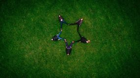 5 Person Laying on Green Grass Field Forming Star Royalty Free Stock Photo