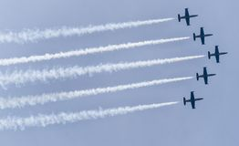5 planes flying in acrobatic formation. Five acrobatic aircraft flying in the sky with smoke behind Royalty Free Stock Photo