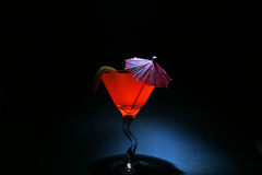 About a 5 second time laps aka Bulb exposure of orange liquid in a martini glass lit up with a. Small flash light with a pink drink umbrella and lemon twist royalty free stock photography