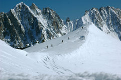 5 Skiers on the Arret du Midi. 5 Skiers making their way along the ridge that continues from the Arret du Midi with the Drus in the background in the Mt Blanc Royalty Free Stock Photos
