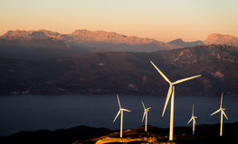 5 White Wind Turbines on Mountain Slope Near River Stock Image