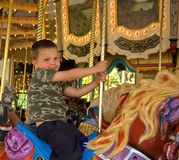 5 Year Old Boy on Carousel Horse. This cute Caucasian 5 year old boy is riding a carousel horse and having a classic childhood memory Stock Photography