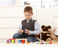 5 year old with toys. 5 year old kid playing with toys on floor, smiling stock photo
