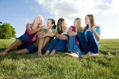 5 zusammen sitzende und lachende Mädchen Stockbild
