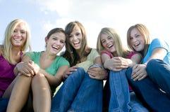 5 zusammen sitzende und lachende Mädchen Stockbilder