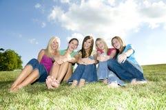 5 zusammen sitzende und lachende Mädchen Lizenzfreie Stockfotos