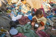 当她的父母在转储时,工作孩子坐 在尼泊尔年年死50,000个孩子,在60%案件-营养不良中 免版税库存图片