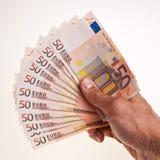 50 euro- notas de banco prendem pela mão masculina direita. Imagens de Stock