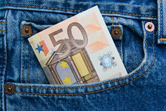 50 euro note in a blue jeans pocket. 50 euro banknote in a blue jeans pocket Stock Image