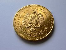 50 pesos gold angle. Gold coin of 50 pesos mexcain at angle featurig eagle and snake Stock Image