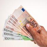 50 y 100 billetes de banco euro se sostienen a disposición. Imagen de archivo