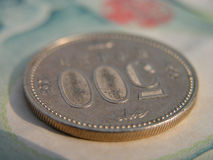 500 yen coin. Interesting perspective of a 500 yen coin on a 1000 yen bill Stock Photo