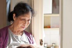 50s亚洲妇女读取报纸在家 库存图片