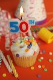 50th birthday. Delicious cupcake with 50th candle on top with hat, candle and noisemaker in background Stock Photography